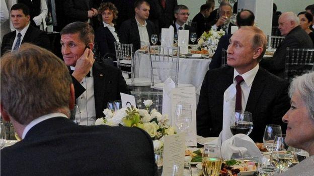 In this file photo taken on 10 December 2015, Russian President Vladimir Putin is seen centre right with retired US Lt Gen Michael Flynn, center left
