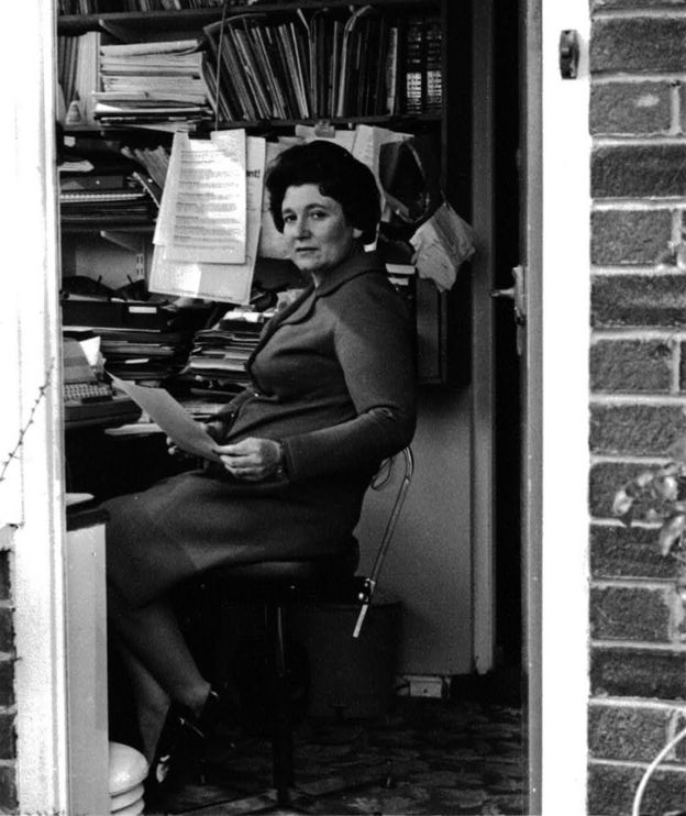 Diane Munday, sitting at a desk in the 1960s