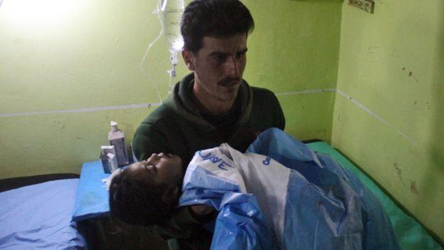 Un hombre carga a una niña inconsciente.