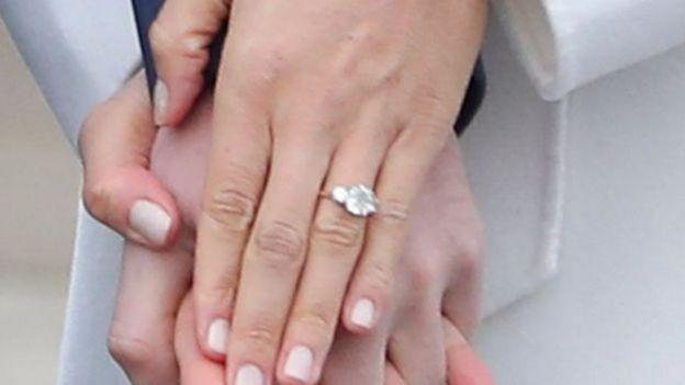 马克尔还向记者显示她戴的钻石订婚戒指。