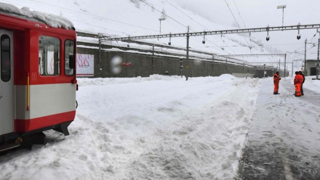 Trains remain blocked by snow on the railway tracks at the Zermatt train station on January 09, 2018.