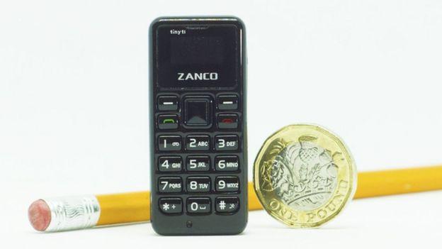 Imagen del teléfono al lado de una moneda.