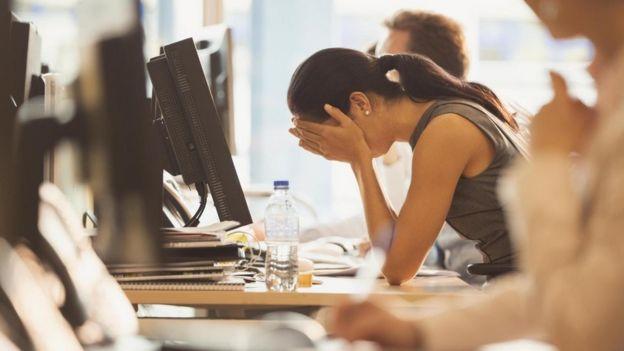 Una mujer, agobiada, con el rostro entre las manos, apoyada en su escritorio
