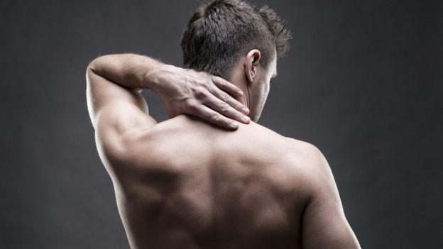 Homem com mão nas costas, como quem sente dor