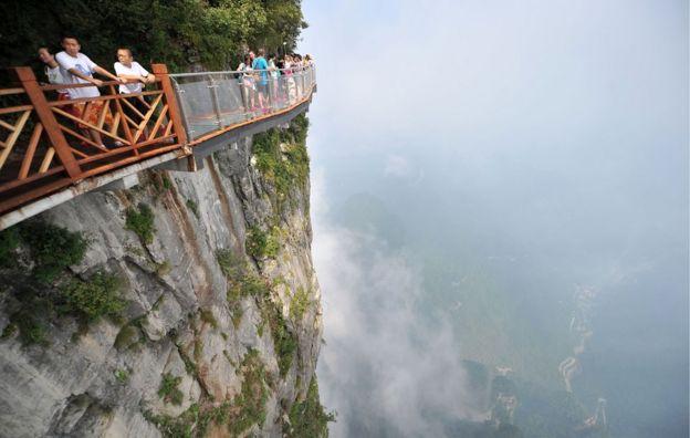 Pessoas caminham sobre ponte de cristal