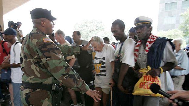 Un soldado intenta poner orden en la fila de acceso al estadio Superdome de Nueva Orleans.