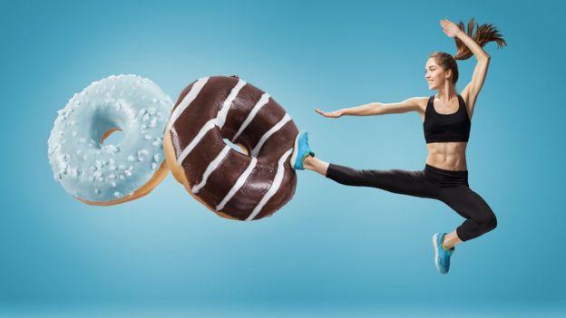 Mujer en forma pateando dos donuts gigantes.