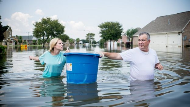 Jenna Fountain and her father Kevin carry a bucket down Regency Drive to try to recover items from their flooded home in Port Arthur, Texas, September 1, 2017