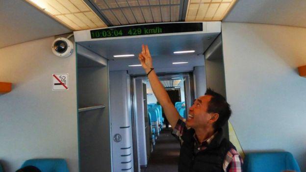 Un pasajero señalando un generador de caracteres dentro del tren que muestra a qué velocidad viaja