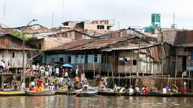 Gente en botes frente a casas en el Amazonas