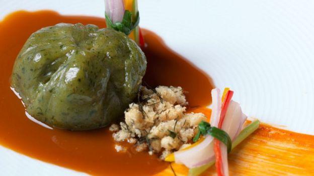 Plato creación de Mitsuharu tiene filamentos de cebolla y pimiento, una suerte de puré verde y una salsa.