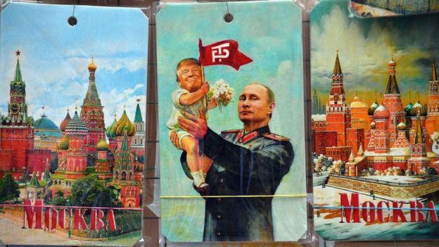 Puesto de venta de souvenirs en donde se ve una tarjeta con Putin elevando a un bebé Trump.