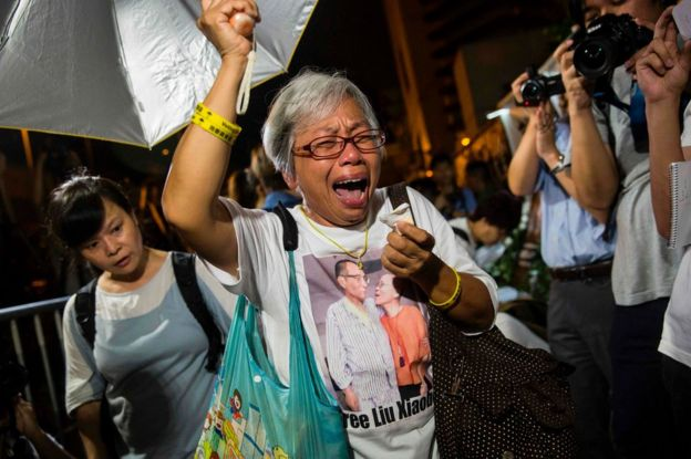 A protester reacts after paying her respects outside the Chinese Liaison Office of Hong Kong after the death of Chinese Noble laureate Liu Xiaobo, in Hong Kong on 13 July 2017