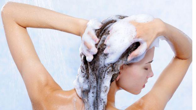 Una mujer se lava el pelo en la ducha