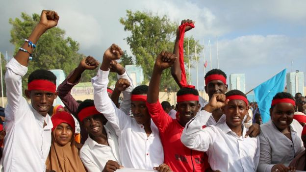 men in red bandanas and white shirts, raising their fists and smiling