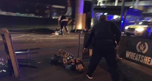 پلیس بر روی سر فردی که برزمین افتاده است (آنچه در این عکس بر تن مردی است که به زمین افتاده یک جلیقه قلابی است که شبیه مواد منفجره است)