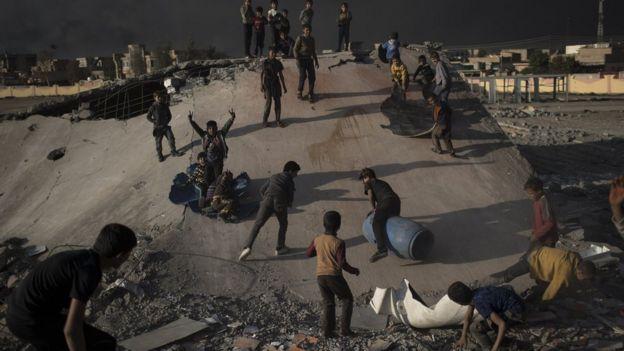 Crianças brincam de escorrega com destroços