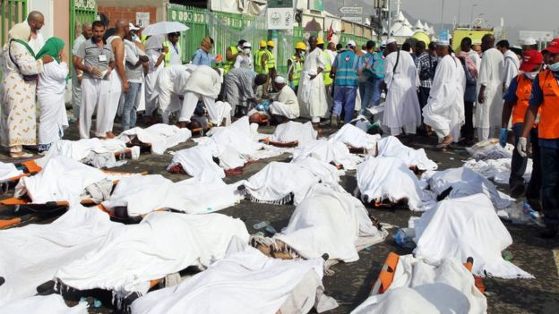 Saudi emergency personnel stand near bodies of Hajj pilgrims at the site where at least 717 were killed and hundreds wounded in a stampede in Mina, near the holy city of Mecca, at the annual hajj in Saudi Arabia on September 24, 2015.