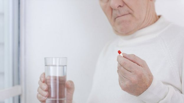 Elderly man taking pill