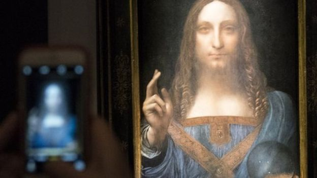 Someone takes a smart phone image of the painting in a darkly lit room