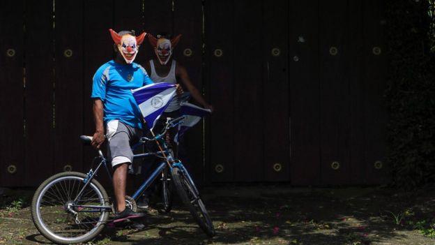 Dos jóvenes con máscaras de payaso y banderas de Nicaragua