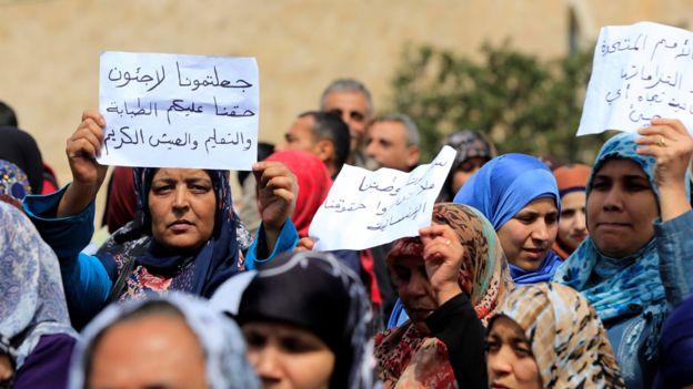 Mujeres y hombres palestinos en una protesta en Líbano por la falta de ayuda