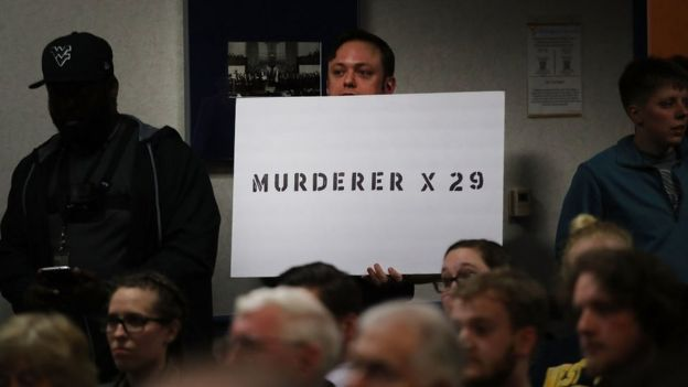 protester holds sign accusing Blankenship of murder