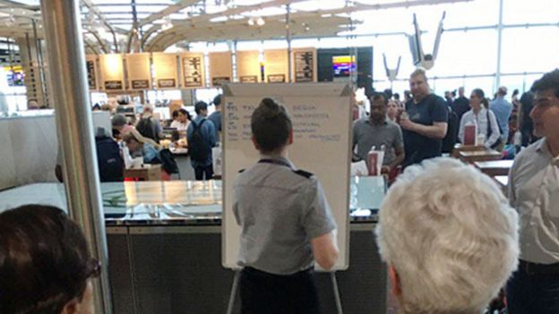 a member of British Airways staff writing gate information on a white board at Heathrow Airport