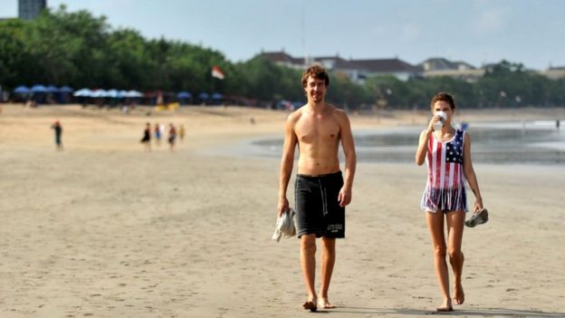 Foreign tourists are pictured walking along a beach