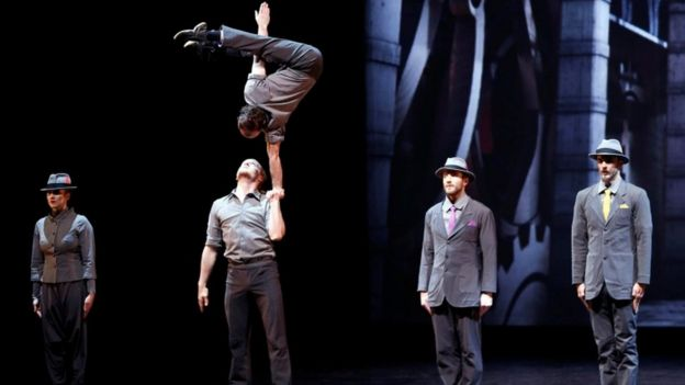 A group of circus performers: one man balances on another's palm,