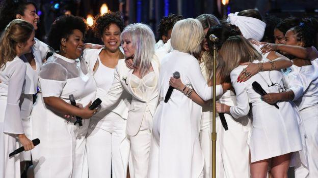 Las cantantes que acompañaron a Kesha en su presentación la abrazan al final de la misma.