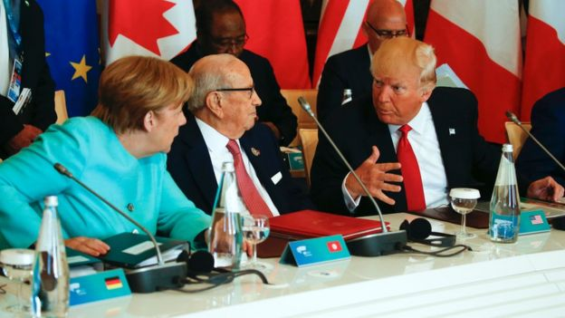 President Donald Trump talks to German Chancellor Angela Merkel (L) and Tunisia's President Beji Caid Essebsi at the G7 Summit on May 27, 2017 in Taormina, Sicily