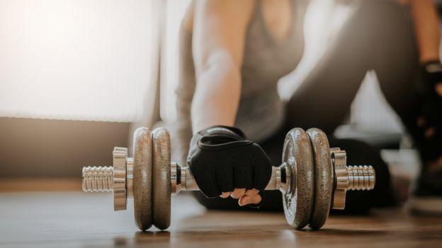 Una mujer agarrando una pesa.