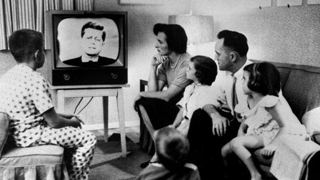 Familia estadounidense en los 60 con una imagen del presidente John F. Kennedy en el televisor.