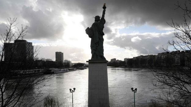 A picture taken on January 26, 2018, shows the flooded Ile aux Cygnes and banks of the River Seine with a model of the Statue of Liberty in Paris.