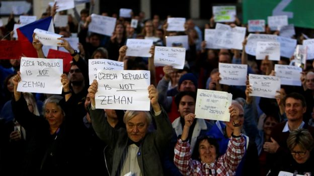 Demonstrators hold signs during a protest rally demanding President Milos Zeman to resign on 17 October 2017
