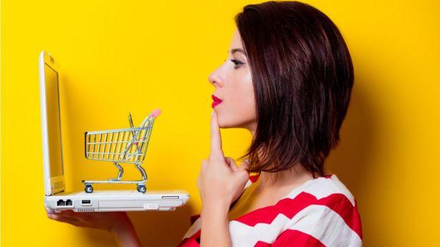 Una mujer con una computadora portátil y un carrito de compras.