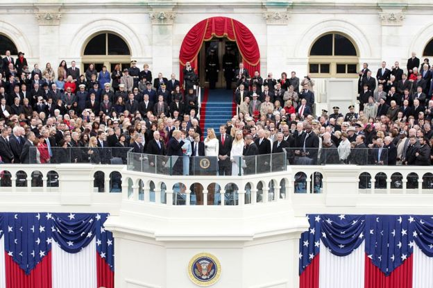 A photo from a distance captures Mr Trump raising his hand as he takes the oath of office as his family and various officials and dignitaries look on