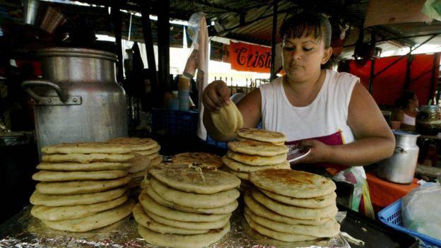 Mujer haciendo pupusas en El Salvador