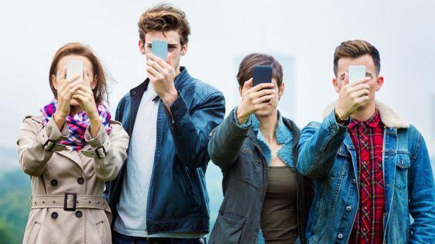 Jovens com celular na frente do rosto