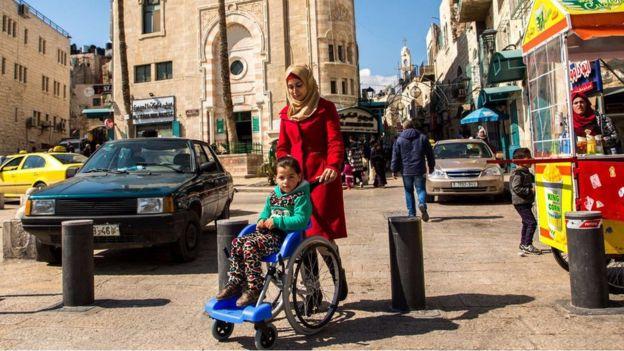 Madre llevando a niña en silla de ruedas en Palestina