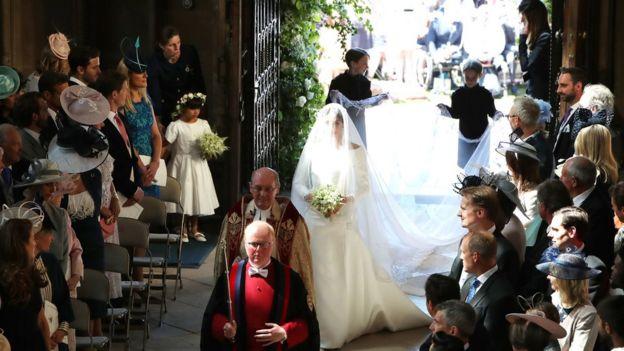 Noiva entra na capela, com crianças carregando a calda do vestido