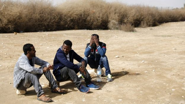 Three African men sit outside Holot detention facility near the Israeli-Egyptian border in southern Israel, 22 February 2018