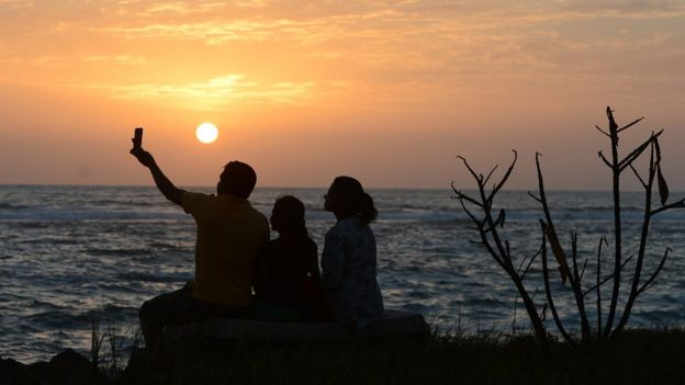 A Sri Lankan family takes a selfie at sunset on a beach in Colombo