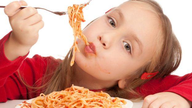 Niña comiendo espagueti con salsa boloñesa