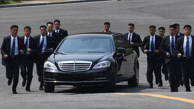 Bodyguards run alongside a car carrying North Korean leader Kim Jong-un as he returns to the North for a lunch break following a morning session of the inter-Korean summit in Panmunjom, 27 April 2018