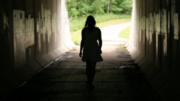 Mulher caminha em túnel