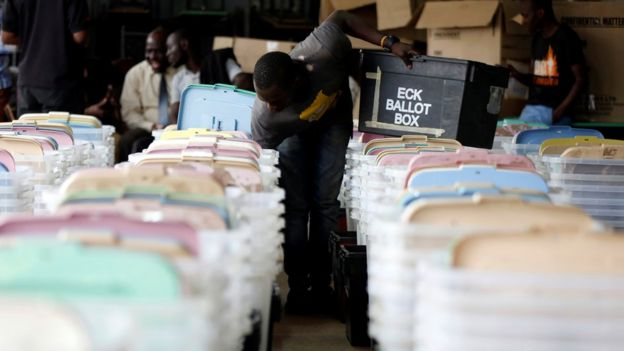 A Kenyan election tallying officer stuffs voting material into ballot boxes before they are transported to different polling stations in the Kibra Constituency at a tallying centre in Nairobi