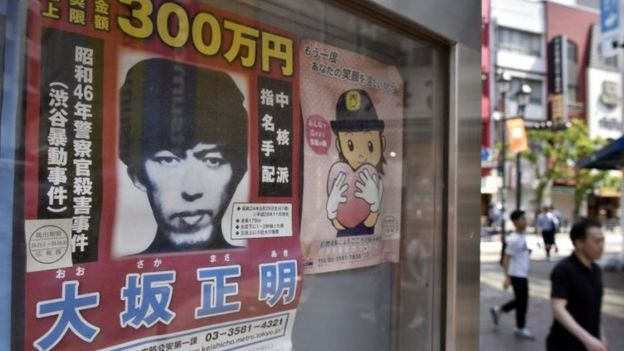 Pedestrians walk past a wanted poster of fugitive Masaaki Osaka (left) displayed at a police box in Tokyo (23 May 2017)