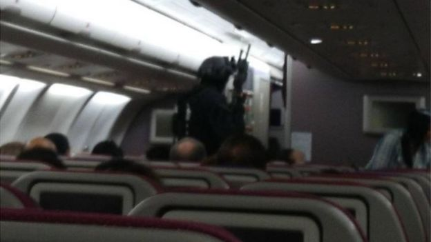 A blurry photo shows passengers seated on the plane, while a heavily armed man in full tactical gear and what appears to be a rifle walks towards the front of the plane